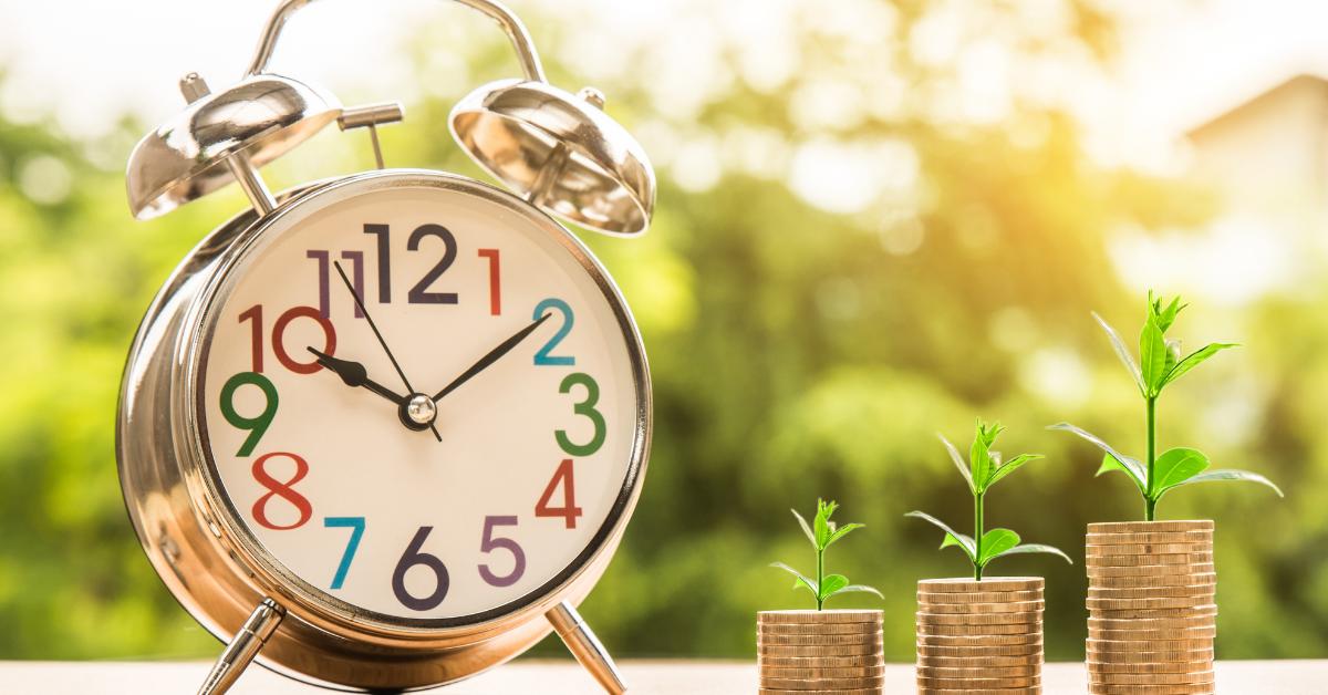 Alarm clock next to growing money